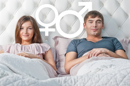 Young couple lying in their bed thinking about something. Gender graphic symbols