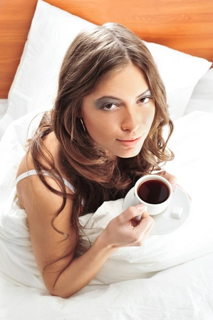 Fashion portrait of young elegant woman in bed at she`s apartment drinking coffee photo
