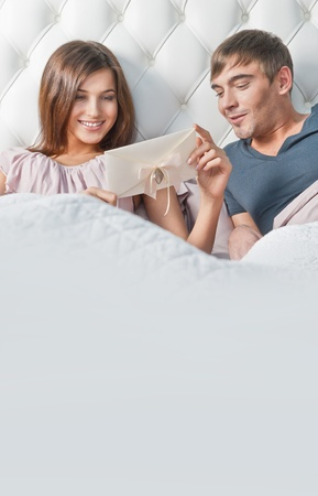 Young happy couple presenting gift in bed photo