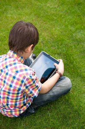 Young boy outdoors on the grass at backyard using his tablet computer. Educating and playing