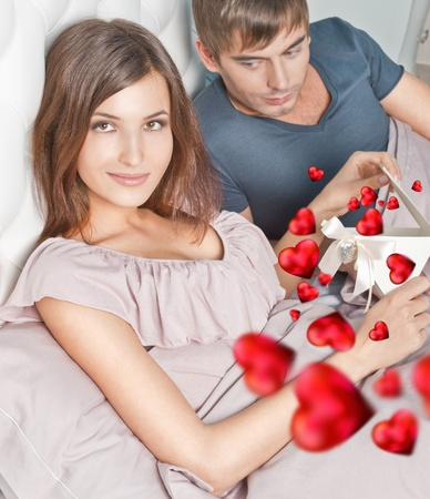 Closeup portrait of a happy young couple relaxing on the bed. Man making a gift to his girlfriend. Saint Valentine`s day concept. Graphic heart. photo