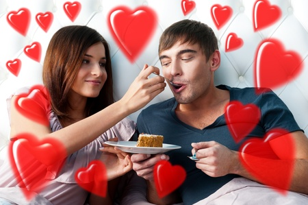 Portrait of happy couple lying in the bed. Girl feeding her boyfriend with spoon of tasty cake. Beautiful graphic red hearts are flying around photo