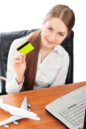 Closeup portrait of young pretty woman at her workplace holding credit card. Online tickets order concept photo