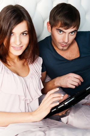 Young couple browsing internet on tablet computer while sitting in bed photo