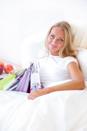 uitpakken: Jong gelukkig aantrekkelijk meisje uitpakken boodschappentassen in de slaapkamer of hotel na te genieten van het zijn in winkelcentrum. Verticale Shot