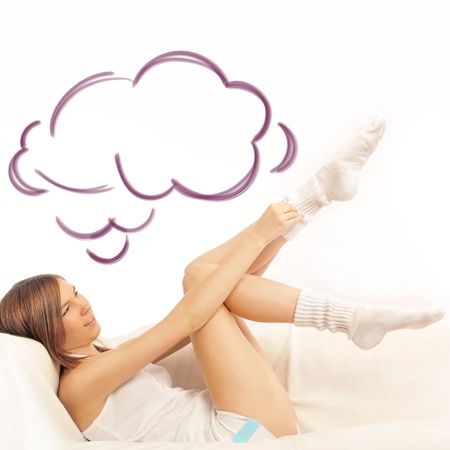 Closeup portrait of beautiful young brunette woman on the bed at home putting up socks and daydreaming with blank cloud balloon overhead photo