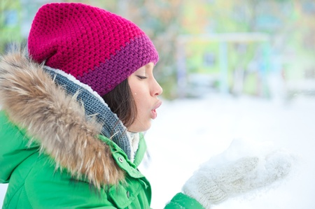 Christmas Girl.Winter woman Blowing Snow. Side View photo