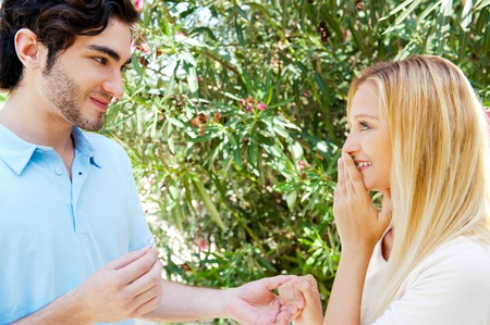 gifting: Happy young hispanic man gifting a ring to a beautiful surprised young caucasian woman in a park Stock Photo