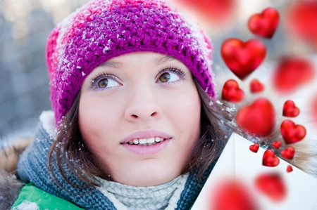 Young lady outdoors happily holding valentine gift and dreaming photo