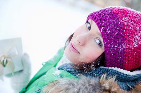 Beautiful and cheerful young lady in a happy mood outdoors in winter photo