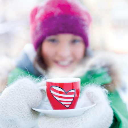 young beautiful girl day dreaming outdoors in winter while having coffee photo