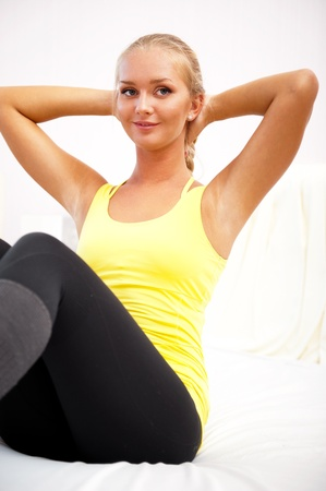 Portrait of beautiful young woman doing exercise at her home photo