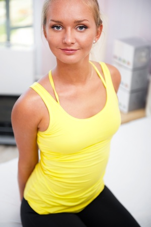 Portrait of beautiful young woman resting after doing exercise at her home photo