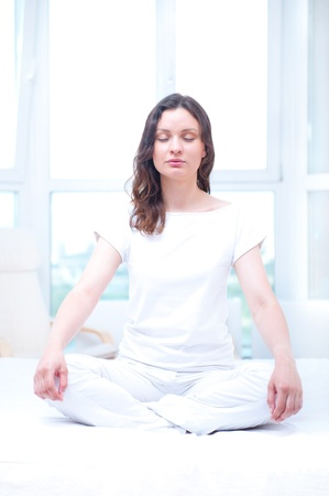 Young woman meditating with closed eyes in bright bedroom sitting on bed photo