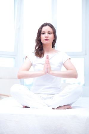 Young woman meditating with opened eyes in bright bedroom sitting on bed photo