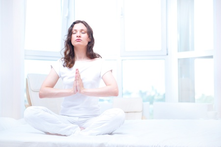 yoga meditation: Young woman meditating with closed eyes in bright bedroom sitting on bed Stock Photo