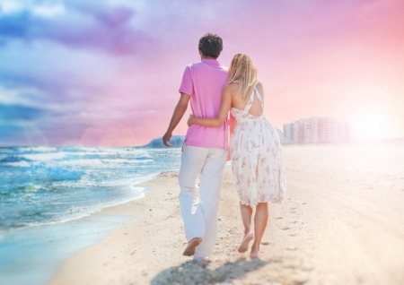 idealistic: Idealistic poster for advertisement. Couple at the beach holding hands embracing and walking. Sunny day, bright colors. Photo from behind.  Europe, Spain, Costa Blanca