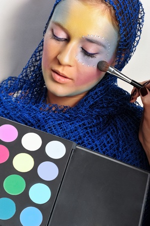 Closeup portrait of young beautiful woman with colorful makeup applying blusher using brush photo
