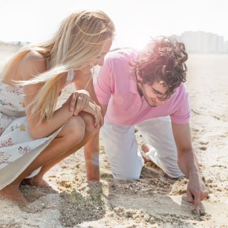 Couple in love drawing a heart in the sand while relaxing at beach photo