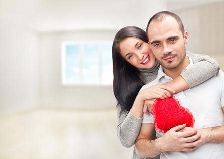 赤いハートの自宅で立っていると受け入れと若いカップルの肖像画。彼らは一緒に本当に満足しています。