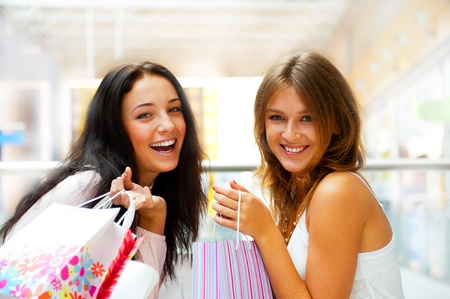Two excited shopping woman together inside shopping mall laughing and gossip. Horizontal Shot photo