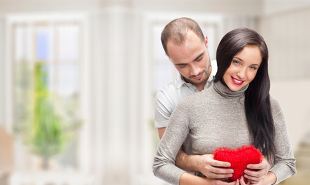 beloved: Portrait of young couple with red heart standing at their home and embracing. They are really happy to be together