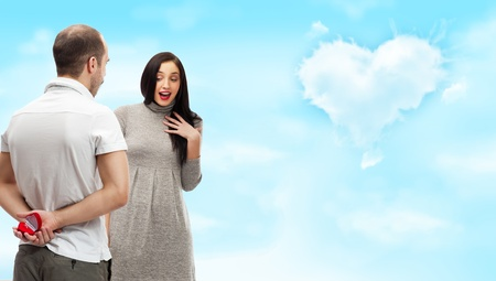 Happy young man gifting a ring to a beautiful surprised young woman on romantic background with sky and clouds of heart shape photo
