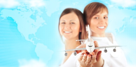 Portrait of two young happy women stewardess holding jet aircraft in their arms on foreground against world map. Advertisement banner for transport companies with worldwide concept photo