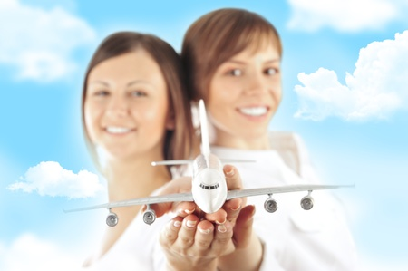 Portrait of two young happy women stewardes holding jet aircraft in her arms on foreground. Advertisement banner for transport companies photo