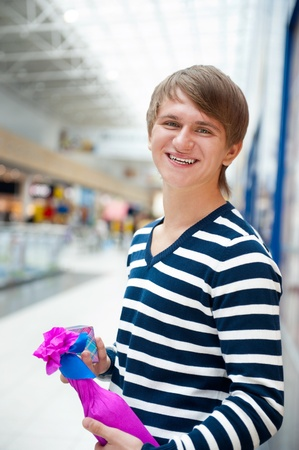 make a gift: Portrait of young man inside shopping mall standing relaxed and holding gift box and bottle. He is preparing to visit his girlfriend and make a proposal