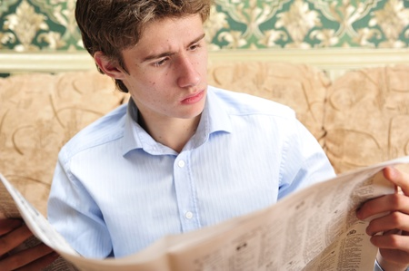 evening newspaper: Closeup portrait of young man with newspaper sitting on his sofa  Retro style photo