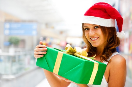 Portrait of young excited pretty woman wearing Santa Claus helper hat standing inside shopping mall smiling and holding christmas gift. photo