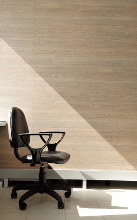 quiting: Portrait of a lone office chair facing the right. Office background.