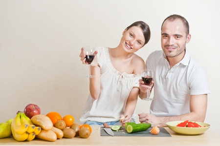 Young love couple cooking and drinking red whine from beautiful glasses. Big copyspace photo