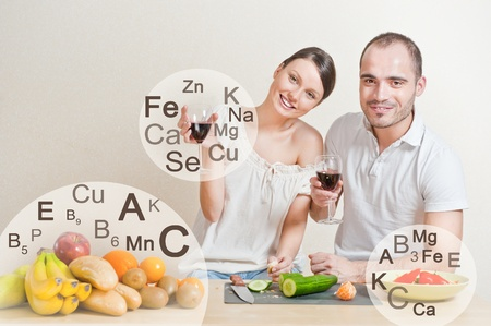 helthcare: Young lovely couple cooking a balanced diet. Big copyspace. Vitamins and microelements symbols are around them.