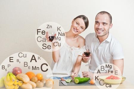 alimentacion balanceada: Encantadora pareja joven cocinar una dieta equilibrada. Gran copyspace. Vitaminas y microelementos s�mbolos est�n a su alrededor.