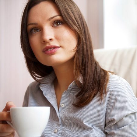 Young woman at home sipping tea from a cup sitting on comfortable armchair near big window photo