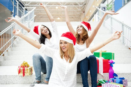 Group of three beautiful girls sitting on stairs at shopping mall hall wearing santa clause red hats with open arms photo