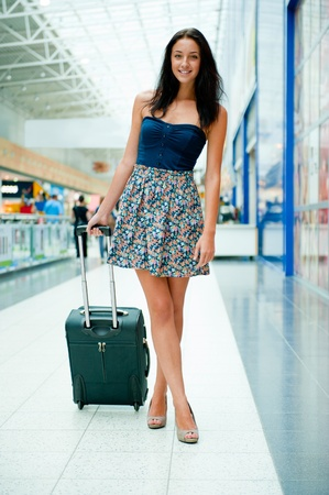 Young woman with luggage at the international airport. She is very happy of her vacation at warm country on christmas holidays photo