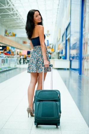 Elegante mujer bonita joven con el equipaje en el aeropuerto internacional. A la espera de su vuelo en la zona libre de impuestos de compras. Foto de archivo