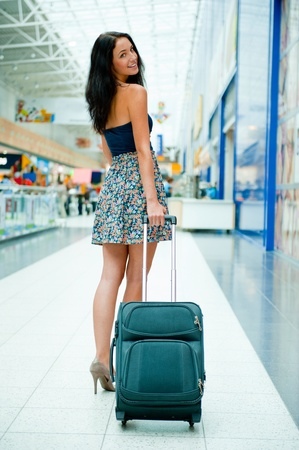 Young pretty stylish woman with luggage at the international airport. Waiting her flight at tax free shopping zone. photo