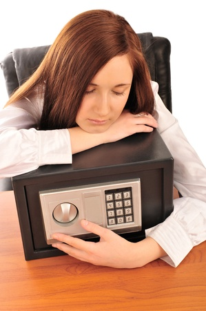 Closeup portrait of young pretty woman at her desk with deposit safe  photo