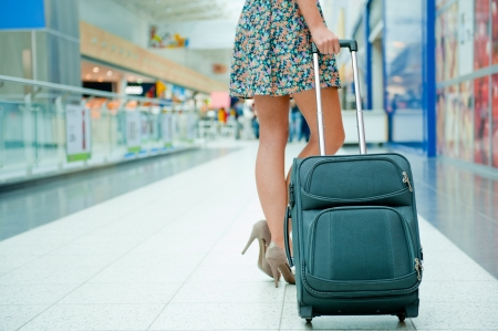 Womans legs and travel suitcase at international airport tax free shopping zone photo