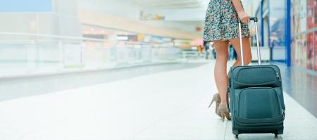 Piernas de la mujer y la maleta de viaje en zona comercial libre de impuestos aeropuerto internacional