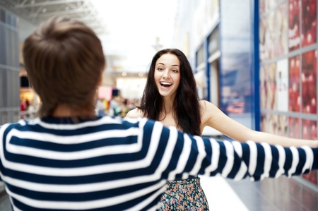 Young man meeting his girlfriend with opened arms at airport arrival hall Stock Photo