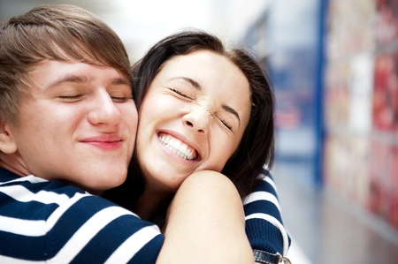 open girl: Young man meeting his girlfriend with opened arms at airport arrival hall Stock Photo
