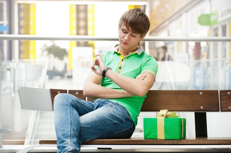 Portrait of young man inside shopping mall with gift box sitting relaxed on bench and waiting for his girlfriend photo