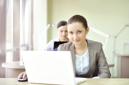 coporate: Portrait of two women working at their desks  Office background