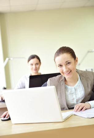 coporate: Portrait of two women working at their desks. Office background.