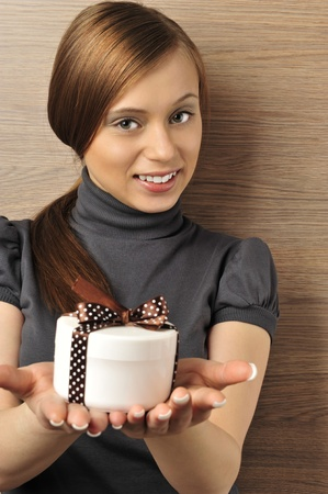 coporate: Portrait of a beautiful young woman offering a present. Office background. Stock Photo